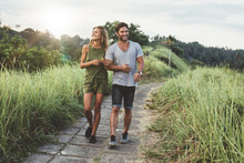 Young Couple In Love Walking On Pathway Through Grass Field