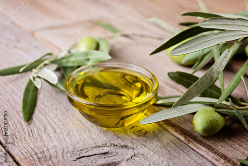 Tuinposter Olijfboom Olive oil and branches on a wooden rustic background