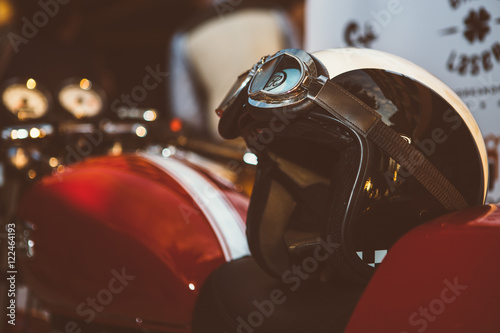 Tuinposter Fiets Moto helmet with vintage glasses on red motorbike