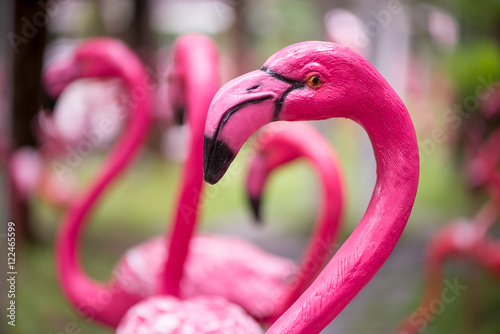 Foto op Aluminium Flamingo Close-up detail of a pink flamingo sculpture decorating a lawn, with a blurred out background. Home and garden decoration concept.