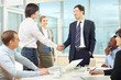 Businessmen handshaking while business people sitting at the table