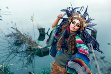 Beautiful Girl Dressed In Native American Indian Clothes, With Paint Face Camouflage And Headdress With Black Feathers And Fur Dancing And Looking In The Sky In Front Of Lake.
