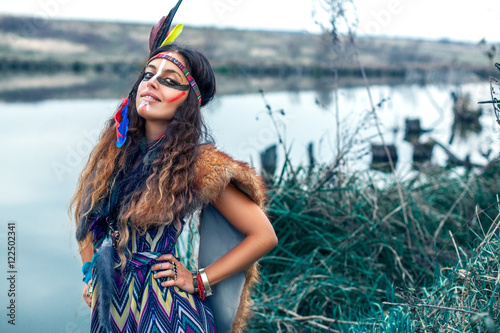 7872113be Beautiful Native American Indian girl dressed in colorful dress, with paint  face camouflage and headdress