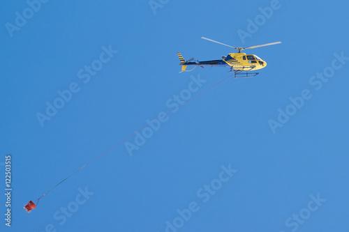 Fotografering  Gelber Hubschrauber transportiert Betonkübel im Baustelleneinsatz