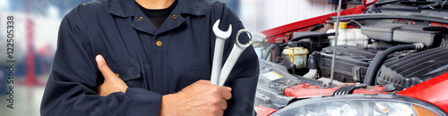 plakat Hands of car mechanic with wrench in garage.