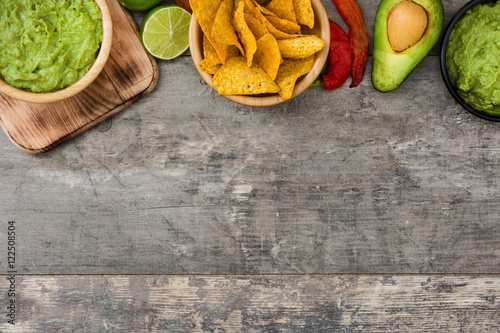 Fotografía  Nachos, guacamole and ingredients on wooden background