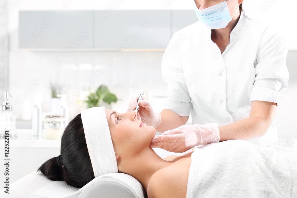 Fototapeta Kobieta w salonie kosmetycznym na zabiegu mezotrrapii mikroigłowej z użyciem rollera.