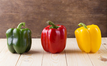 Fresh Sweet Peppers Three Color Red, Yellow, And  Green On Woode