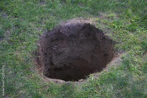 фотография  Deep dirt hole in ground or lawn