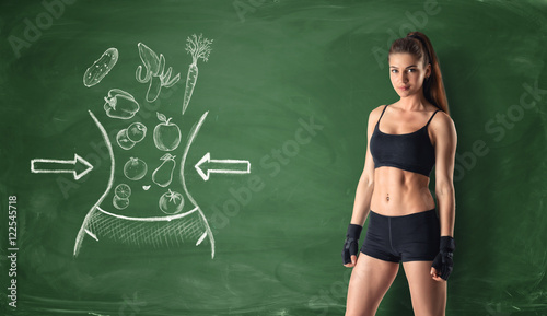 Fitness girl on background of blackboard with healthy food sketches