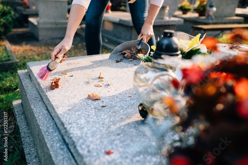 Photo A woman cleans the grave