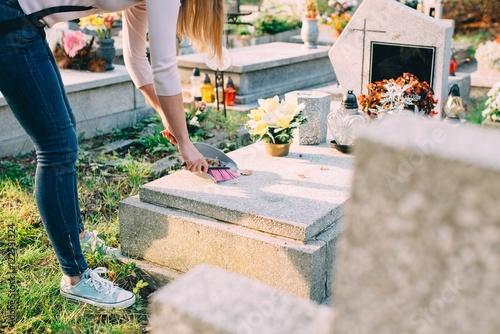 A woman cleans the grave. Fototapeta