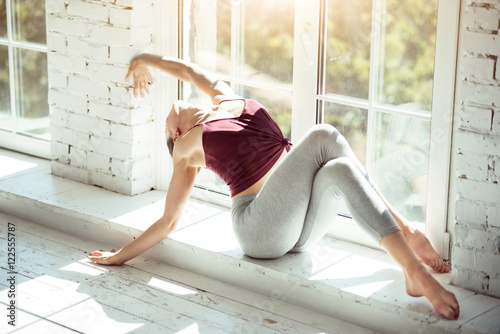 Fotografia  Graceful slender woman sitting near the window