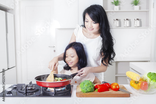 Poster Cuisine Woman and daughter cooking vegetable