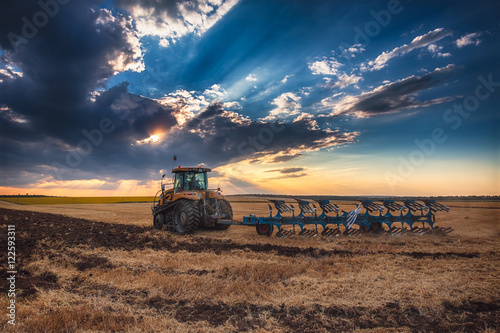 Платно Farmer in tractor preparing land with cultivator