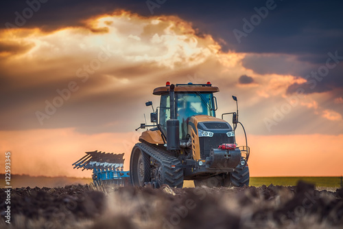 Farmer in tractor preparing land with cultivator плакат
