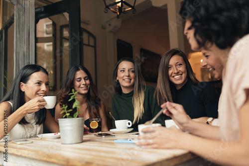 Valokuvatapetti Smiling women having coffee and chatting