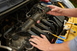 Man change spark plugs outdoor on yellow car