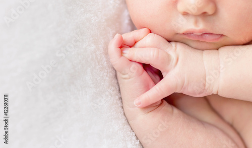 Fototapeta crossed fingers of a newborn baby asleep, closeup obraz