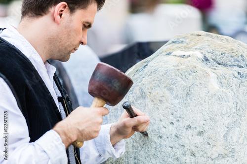 Fotografie, Obraz  Bildhauer mit Meißel und Klüpfel beim Bearbeiten von Naturstein-Block