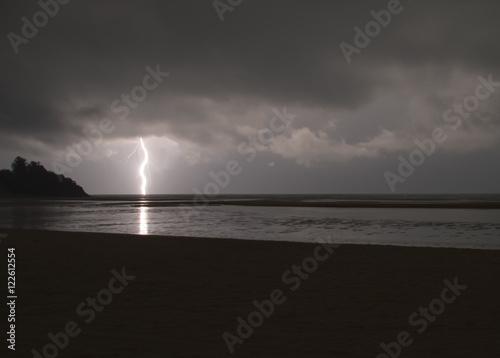 Plakat Niesamowicie ostra błyskawica z gałęziami uderzającymi w ocean odbitym światłem
