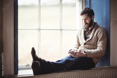 Man using mobile phone while sitting on window sill