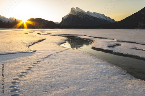 Sun rising beside Mount Rundle, reflecting on ice on snow covered Vermilion Lakes in winter in Banff National Park, Alberta, Canada.