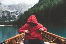 Man With Red Raincoat Rowing A Wood Boat On Braies Lake