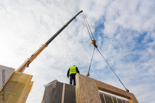 Photo  Roofer builder worker with crane installing structural Insulated Panels SIP