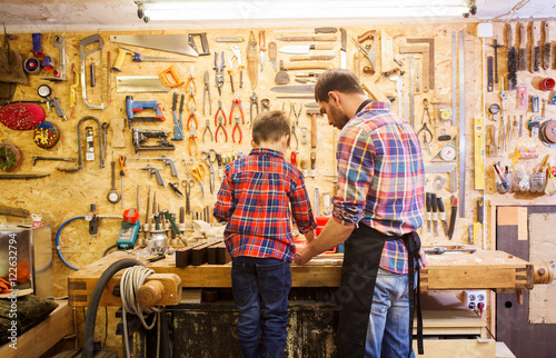 Obraz father and little son with wood plank at workshop - fototapety do salonu