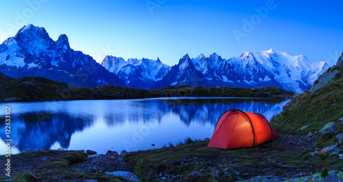 Foto op Canvas Kamperen Red tent at Lac De Chéserys in the mountains near Chamonix, France, during sunrise.