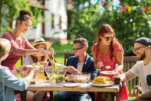 Fotografía  happy friends having dinner at summer garden party