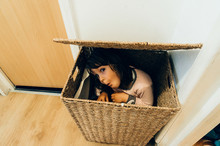 Young Girl Hiding In Basket