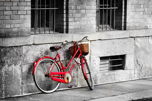 Poster Velo Bright red bicycle on the old street. Black and white filter applied.