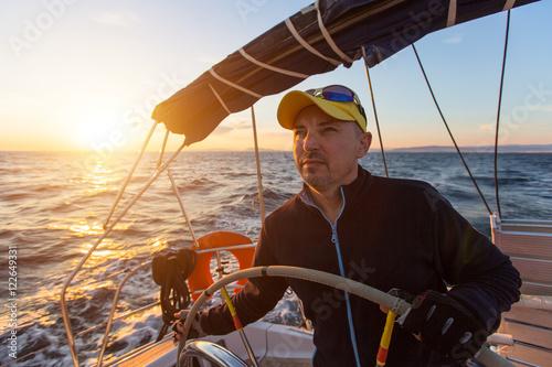 Fotografía  Skipper drives the sailing boat in the Aegean sea.