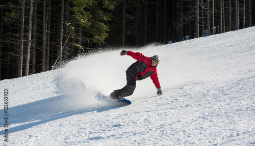 Tuinposter Wintersporten Male snowboarder slides down from the mountain in winter day, overlooking the snowy slope and at a winter resort. Bukovel