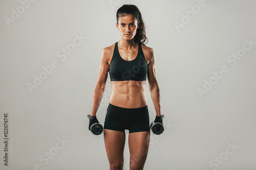 Strong woman with weights and confident expression
