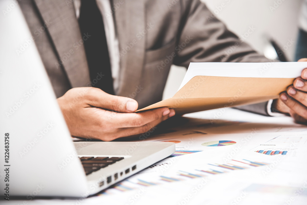 Fototapeta Businessman pulling out business document from brown envelope.