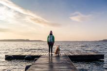 Woman With Dog Enjoy Sunrise At Lake, Backpacker Looking At Beautiful Morning View
