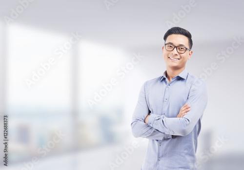 Foto  Lächelnder asiatischer Geschäftsmann in unscharfem Büro