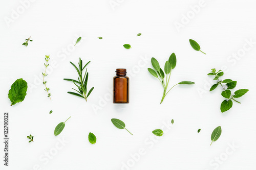 Bottle of essential oil with fresh herbal sage, rosemary, lemon Fototapet