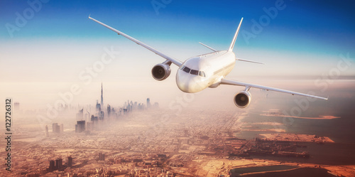 Poster Airplane Commercial airplane flying over modern city