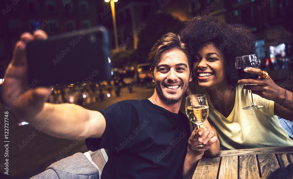 Fototapety, obrazy: Casual interracial couple drinking wine during date and taking a