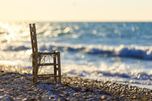 Lone Wooden Chair On The Seashore At Sunset And Waves
