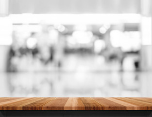 Empty wooden table and blurred shoppping mall bokeh light backgr