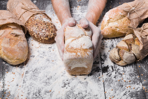 Tuinposter Bakkerij Bakery concept background. Hands hold bread loaf