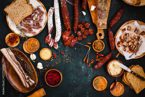 Overhead view of cured meats, sausage with mustard sauce on rustic dark table Canvas