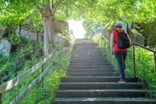 Hiking Woman Climbing The Stone Stairs To Peak