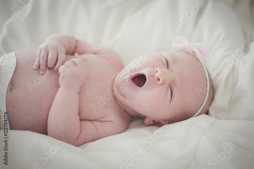 Baby wearing headband yawning while lying on bed at home Poster