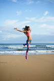 Sporty brazilian woman dancing and jumping at the beach. Black happy dancer practicing dance jumps and having fun outdoor. - 122786127